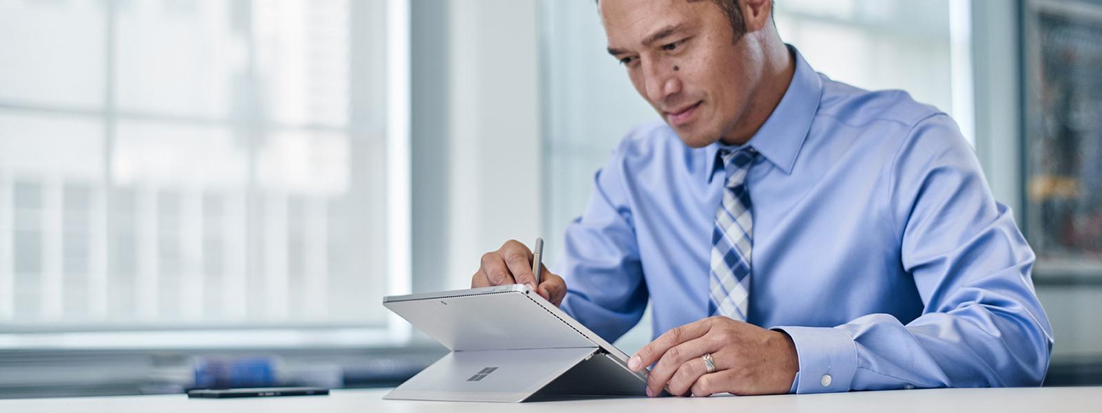 男人坐在桌前,使用 Surface 手寫筆在 Surface Pro 4 上寫字。