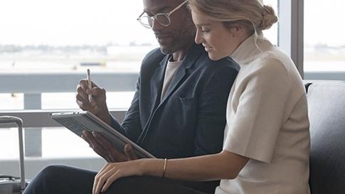 男人在採用平板電腦模式的 Surface Pro 上使用 Surface 手寫筆,並向機場裡坐在他旁邊的女人顯示某個東西。
