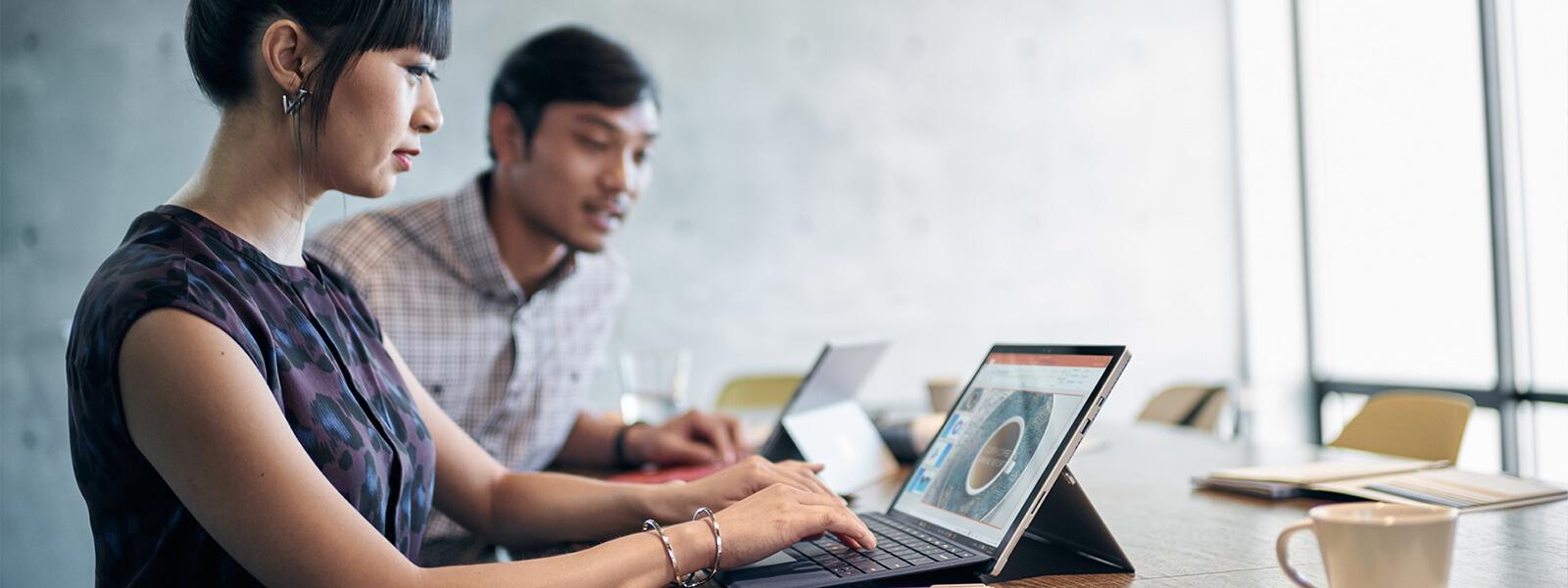 女人在桌上的 Surface Pro 4 裝置上打字。