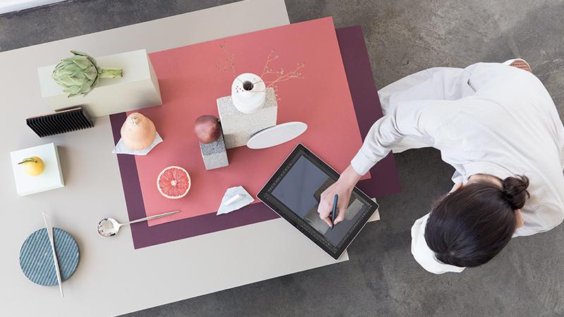 女人坐在桌前使用 Surface Pro。