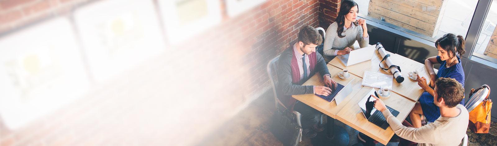 兩位男士及兩位女士坐在咖啡桌旁,一邊以平板電腦使用 Yammer,一邊喝咖啡。