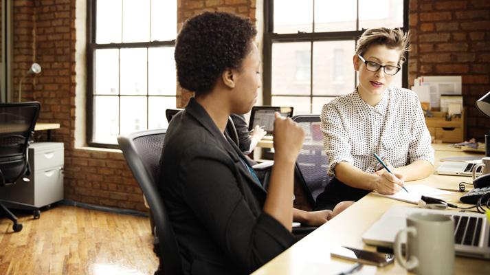 兩位女士坐在書桌前,一位正在用手寫筆記,另一位則在一旁觀看。