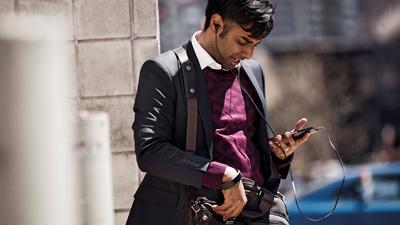 在戶外使用行動裝置並戴著耳機交談的人