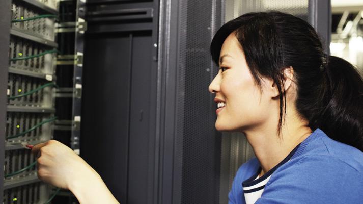 女技術員在資料中心伺服器面板前工作的特寫。