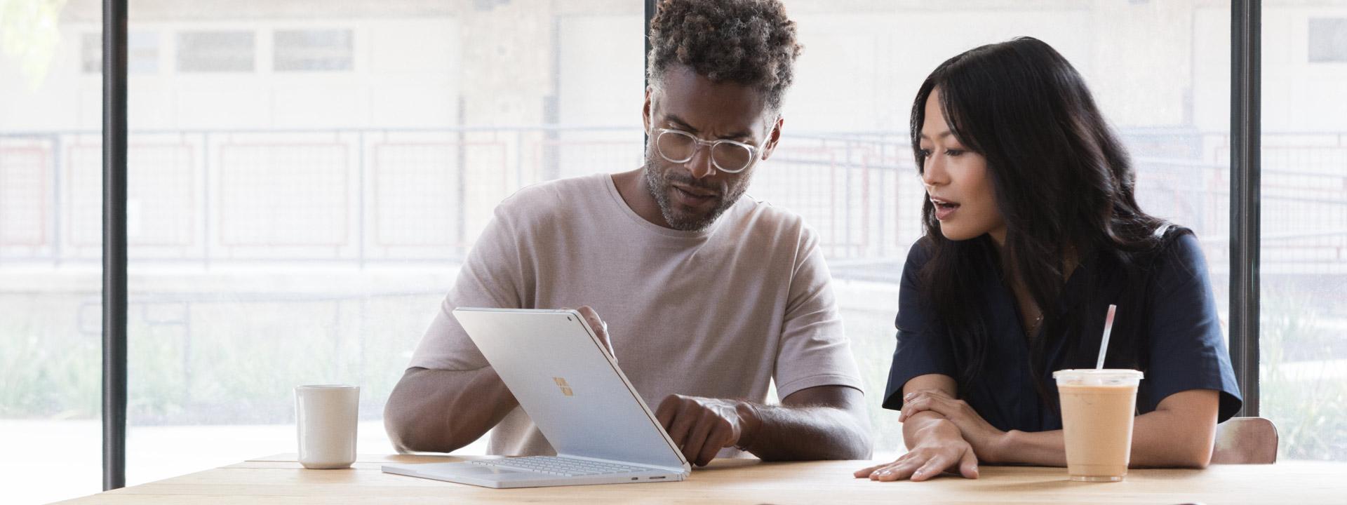 男人和女人在咖啡廳看著鍵盤反折的 Surface Book 2。