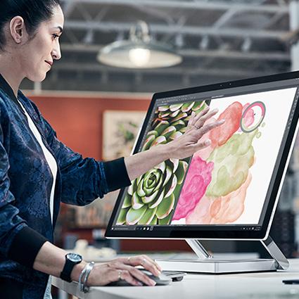男人使用桌上型電腦模式的 SURFACE STUDIO。