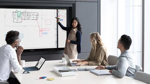 在工作會議中,女人指著 Surface Hub 上的內容