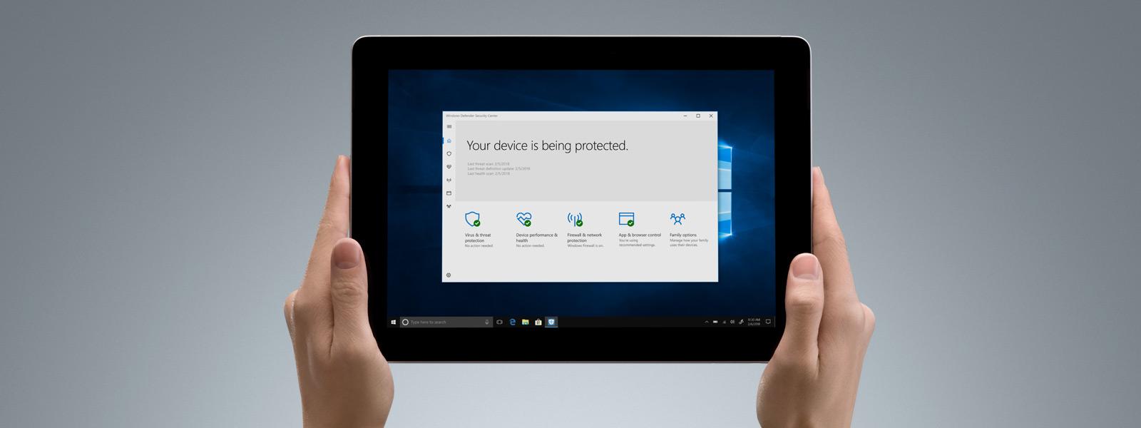像平板電腦般拿著 Surface Go 與 Windows Defender