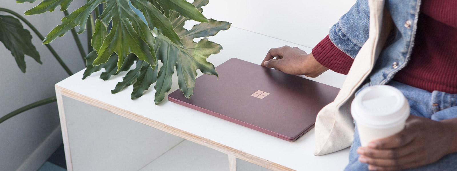 一個人在海灘,在太陽下使用 Surface Laptop 工作的影像。