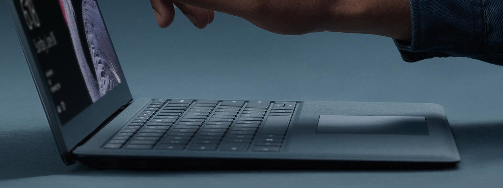強調 Surface Laptop 使用便利、精簡設計且用一隻手就能打開的影像