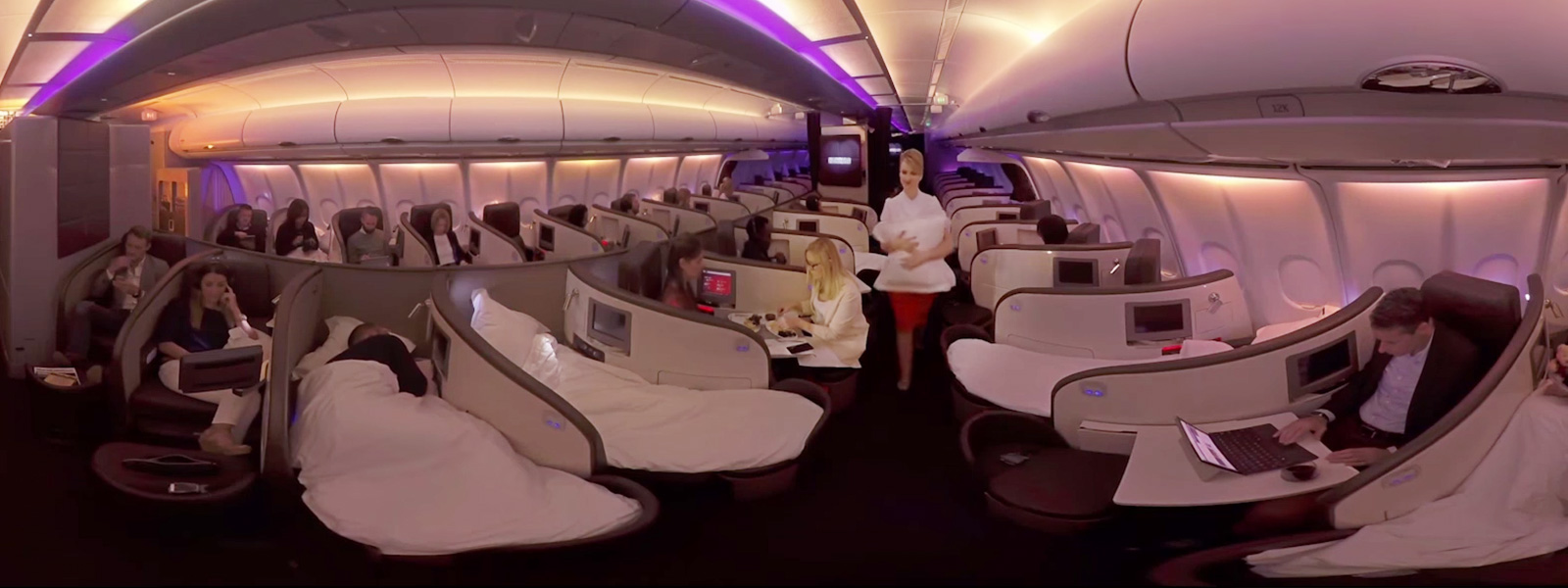 兩位搭乘 Virgin Atlantic 班機的乘客正在使用座位靠頭處上的觸控式螢幕