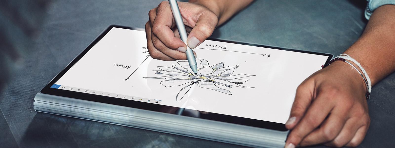 女人使用下移成工作室模式的 SURFACE STUDIO 與 SURFACE 手寫筆。